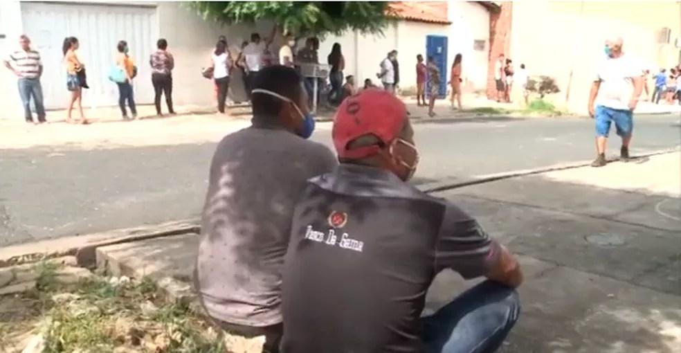 À espera para entrar na agência da CEF em Teresina trabalahdores sentam no chão  — Foto: TV Clube