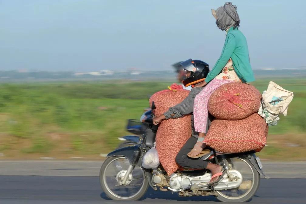 5 de junho - Motociclista leva três sacas de grãos e uma mulher de carona sentada no topo em uma rodovia de Phnom Penh, no Camboja (Foto: Tang Chhin Sothy/AFP)
