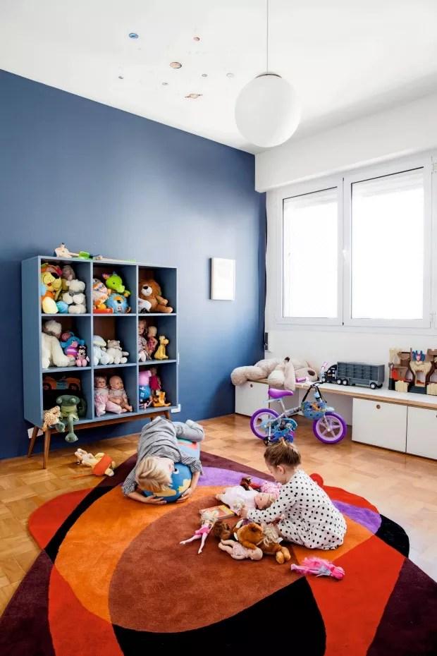 Quarto de brinquedos. Leon e Eva brincam sobre o tapete da Punto e Filo no cômodo que tem uma das paredes pintadas de azul (Foto: Maíra Acayaba / Editora Globo)