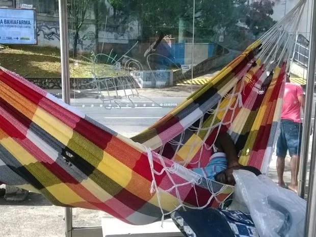 Homem dorme em rede instalada no ponto de ônibus (Foto: Jorge Filho / VC no G1)