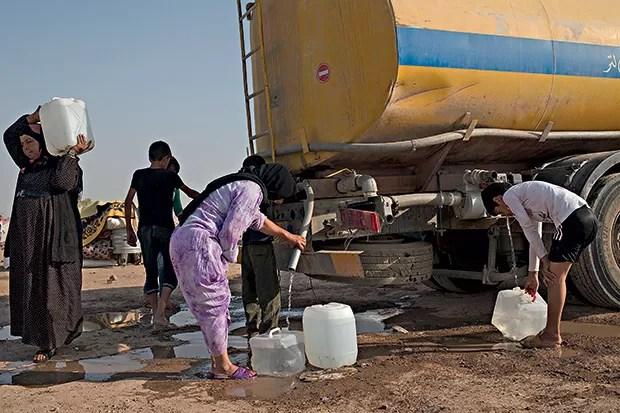 Mulheres e crianças retiram água distribuída pela ONU (Foto: Lynsey Addario/The New York Times)