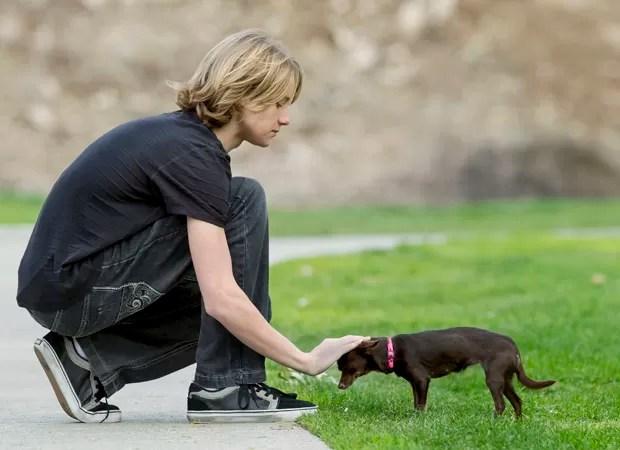 O adolescente americano com o cão Pearl, retirado por ele de um abrigo (Foto: Damian Dovarganes/AP)