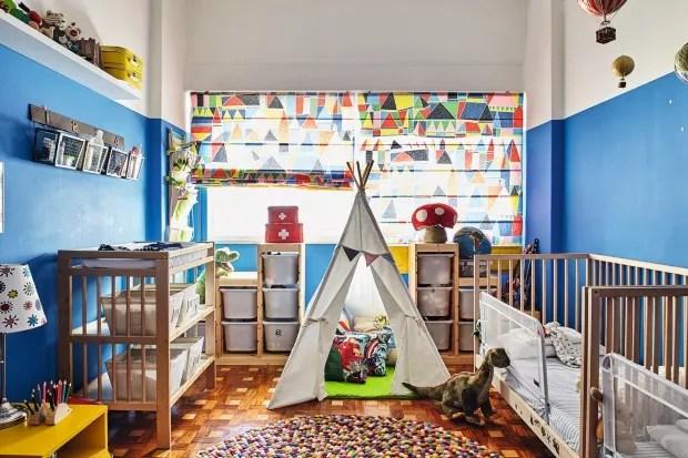Quarto dos gêmeos. A parede ganhou pintura azul royal até a metade. Cortina feita com tecido da Marimekko, camas e organizadores da Ikea. A cabana foi presente de uma amiga (Foto: Victor Affaro / Editora Globo)