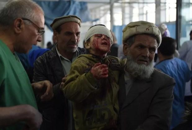 Homem carrega criança atingida por explosão de 'ambulância-bomba' em Cabul, no Afeganistão, neste sábado (27)  (Foto: Wakil Kohsar / AFP)