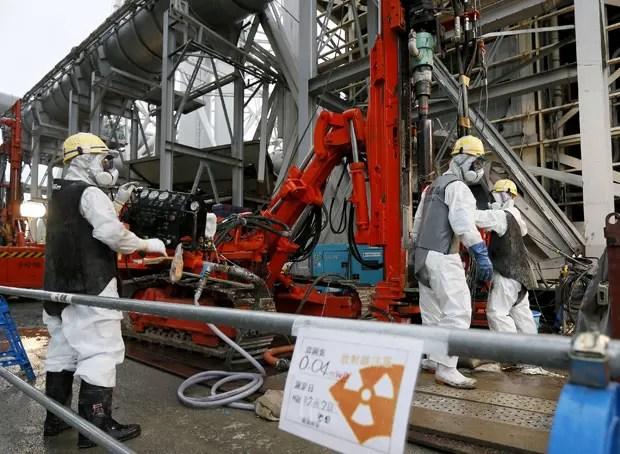 Trio com roupas especiais trabalha na construção de muro de gelo para conter água radioativa de geradores nucleares em Fukushima, no Japão (Foto: Kimimasa Mayama/AP)