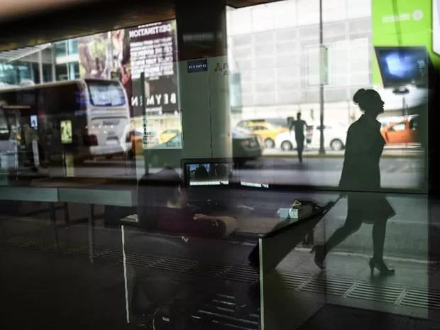 Atrás da sombra de passageira, funcionária analisa imagens do raio-x na entrada do Aeroporto Internacional Ataturk, em Istambul, na Turquia, na manhã desta quarta-feira (29) (Foto: Bulent Kilic/AFP)