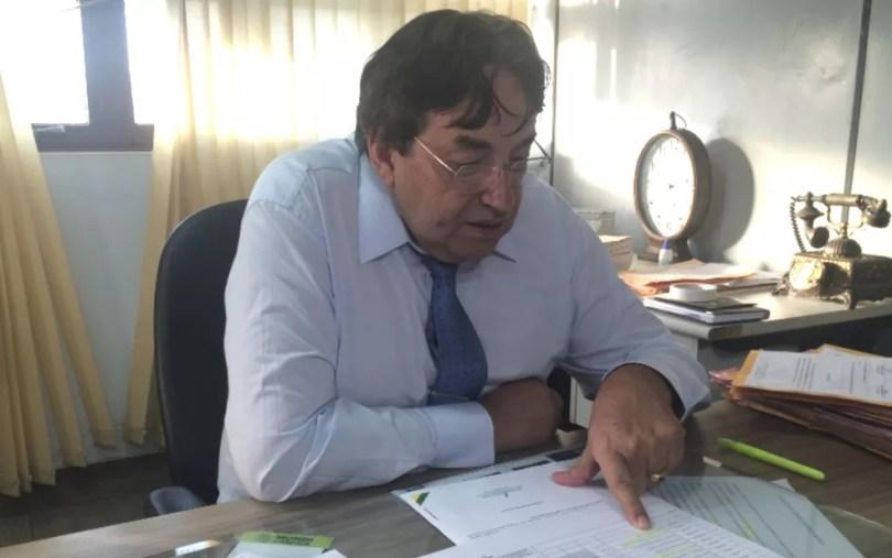 Delegado Izaias Pinheiro analisa documentos apresentados por engenheiro  (Foto: Paula Resende/ G1)