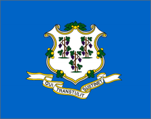"""On a field of azure blue is an ornamental white shield with three grapevines, each bearing three bunches of purple grapes. The states motto """"He who Transplanted Sustains Us"""" is displayed on a white ribbon. The vines stand for the first settlements of"""