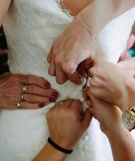 helping bride with her wedding dress
