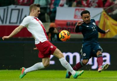 Poland's Lukasz Piszczek and Ikechi Anya of Scotland fight for the ball during their international friendly soccer match in Warsaw