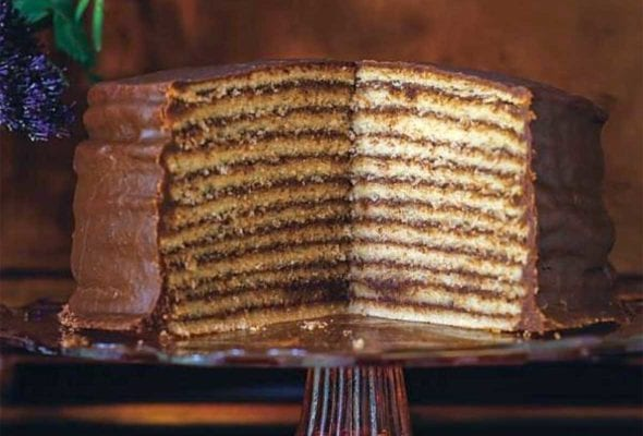 A 12 layer chocolate torte by Trisha Yearwood with chocolate icing on a pink class cake stand