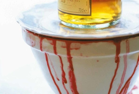 A white bowl with wine dripping down the side topped with a white plate and a bottle of whiskey.