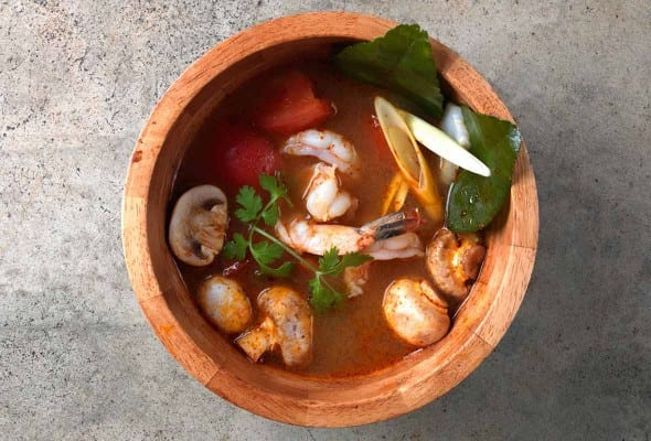 A wooden bowl filled with Tom Yum Goong soup, garnished with cilantro.