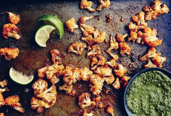 Florets of spicy roasted cauliflower on a baking sheet with squeezed lime wedges and a bowl of green sauce beside them.