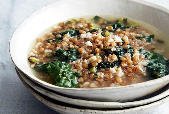 Three stacked white bowls and the top one filled with greens and grains soup, and finished with Parmesan.