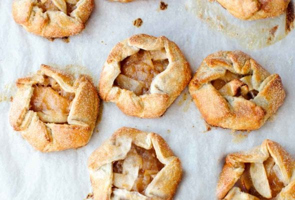 Seven rosemary apple hand tarts on a sheet of parchment.
