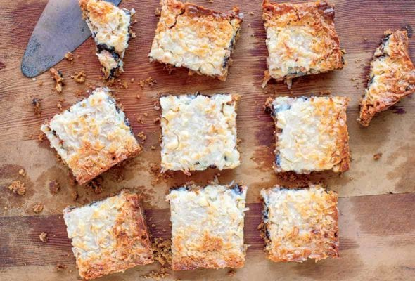 A slab of pumpkin seven layer bars cut into ten pieces on a wooden board.