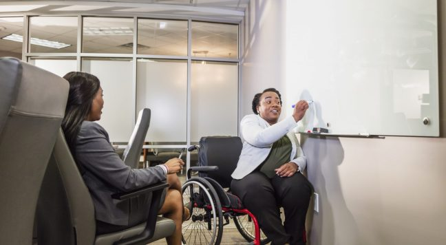 Two African-American businesswomen having a meeting in a boardroom, one in a wheelchair and one in a chair