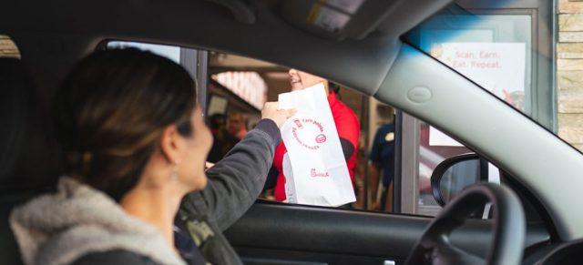 ドライブスルーで食べ物を受け取る女性