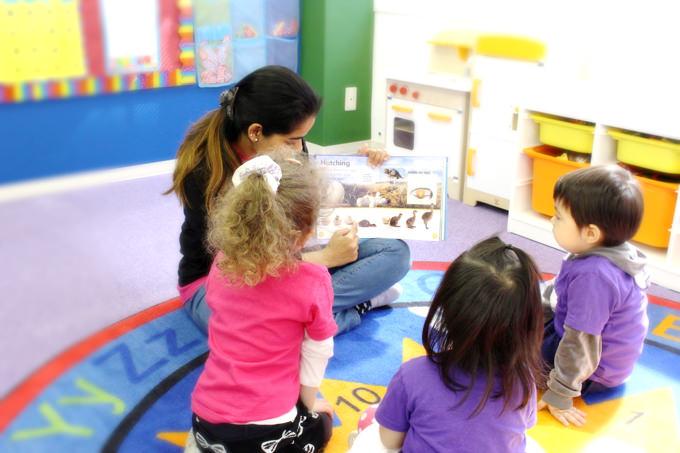 ストーリータイムでは、先生が絵本の読み聞かせをしています。
