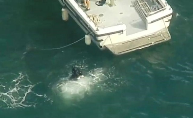 """Diver is seen entering the water from rescue vessel after a seaplane crashed into a Sydney river, killing six people on a """"wine and dine"""" sightseeing flight ahead of the city's harbour-centred New Year's Eve celebrations, in this still image taken from a video on December 31, 2017 via Reuters"""