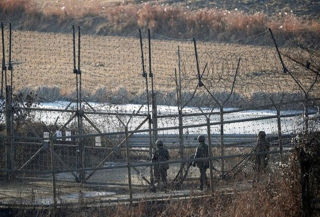 South Korean soldiers patrols along a barbed-wire fence near the demilitarized zone separating the two Koreas in Paju South Korea