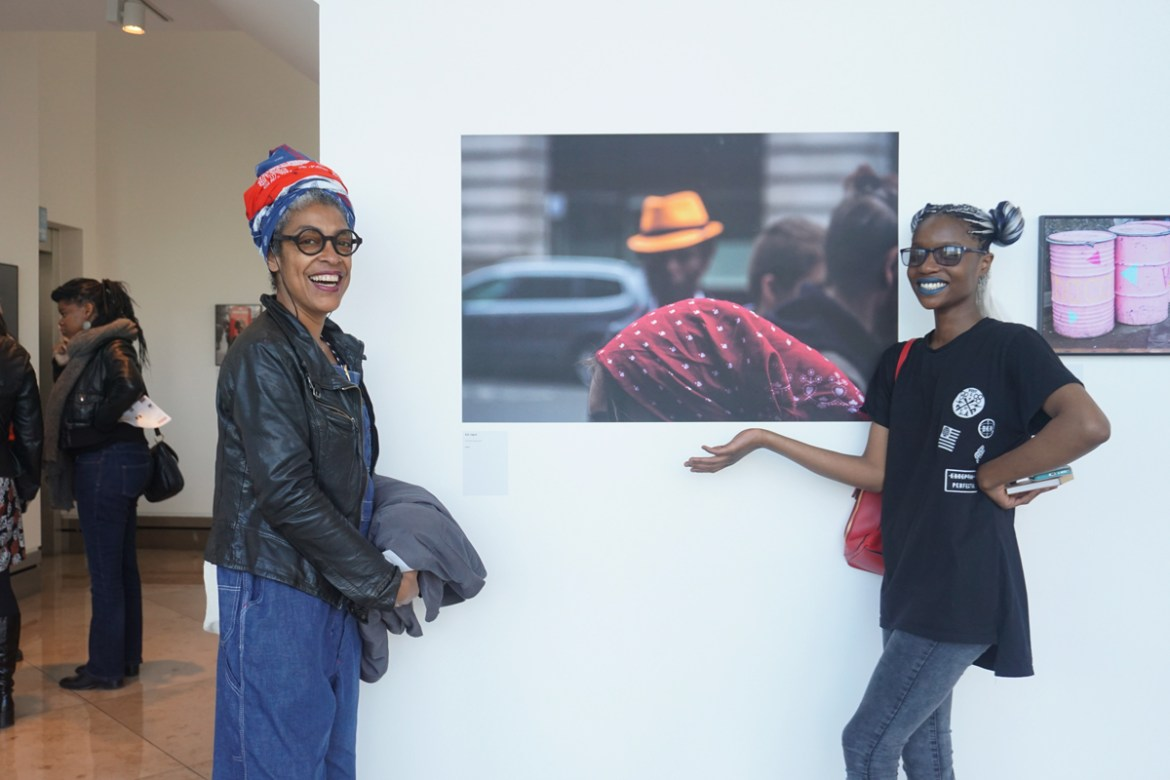 Kat Jagne (right) with one her tutors and her photograph titled 'Red head scarf' at the Made by Us exhibition