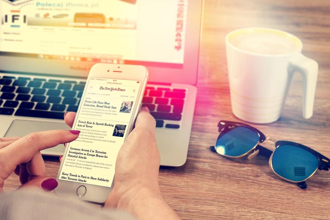 Frau liest auf Smartphone auf Website der New York Times, während sie am Computer sitzt. Foto: Snocksnap