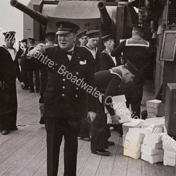 Photo shows WSC on the deck of HMS Prince of Wales. He is wearing a double-breasted jacket and a peaked cap and gesticulating. Behind him are Royal Navy sailors in uniform working to carry piles of boxes [food parcels given to each man as a gift from President Roosevelt].