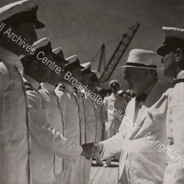 Photo shows WSC smiling as he shakes hands with a man wearing a white naval uniform. A line of men in white naval uniforms and caps stand in front of WSC.