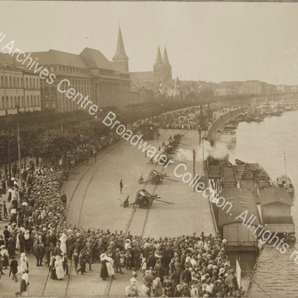 Photograph of field guns being fired on a city riverside [? Cologne