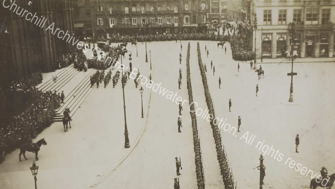 Aerial photograph of two long lines of troops drawn up outside a large building [? Cologne cathedral] in Germany