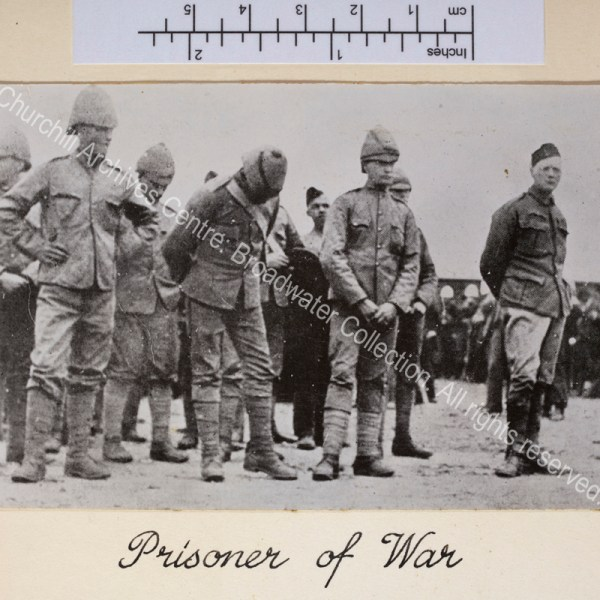 Photograph shows line of prisoners (WSC on the right