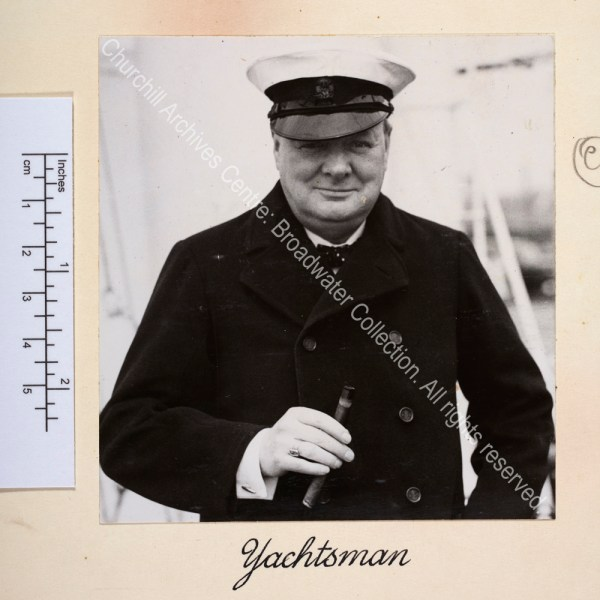 Head and shoulders photo of WSC wearing a yachting cap and holding a large cigar.