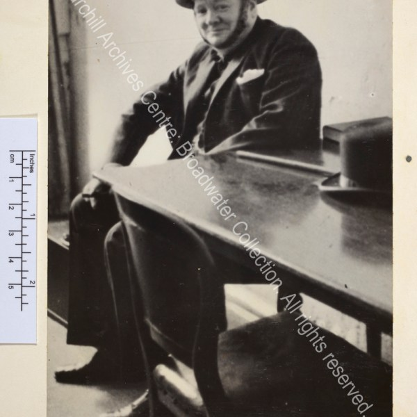 Photo of WSC in Ramsgate [Kent] air raid shelter. Photo shows WSC smiling ruefully wearing a suit and metal helmet. He is sitting next to a table on which rest his Fedora style hat and walking cane.