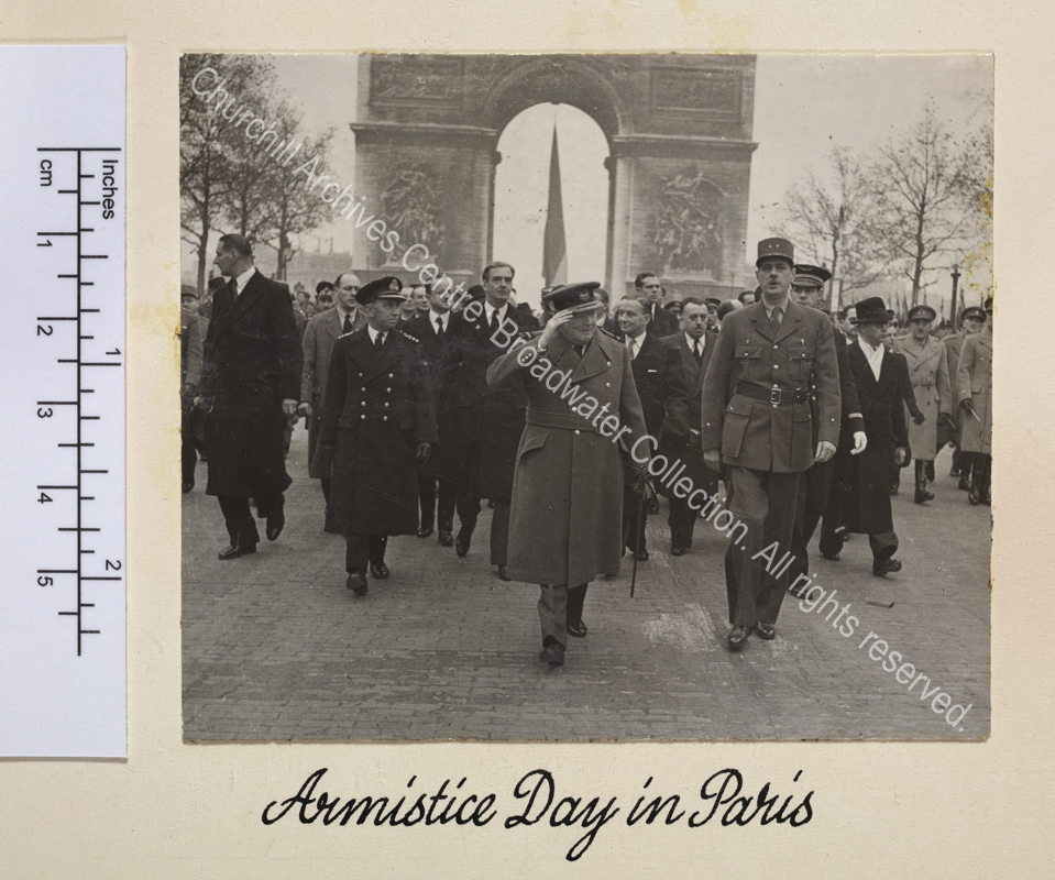 Photo shows WSC and General Charles de Gaulle walking down the Avenue des Champs-Elysee with the Arc de Triomphe behind them during the French Armistice Day parade. Both are in uniform and WSC is raising his hand in salute. Anthony Eden [later 1st Lord Avon] walks behind WSC.