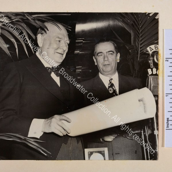 Photo shows WSC on the occasion of receiving the Gold Medal of the City of New York. He is standing in front of microphones smiling and holding a rolled paper. Next to him is Mayor William O'Dwyer.