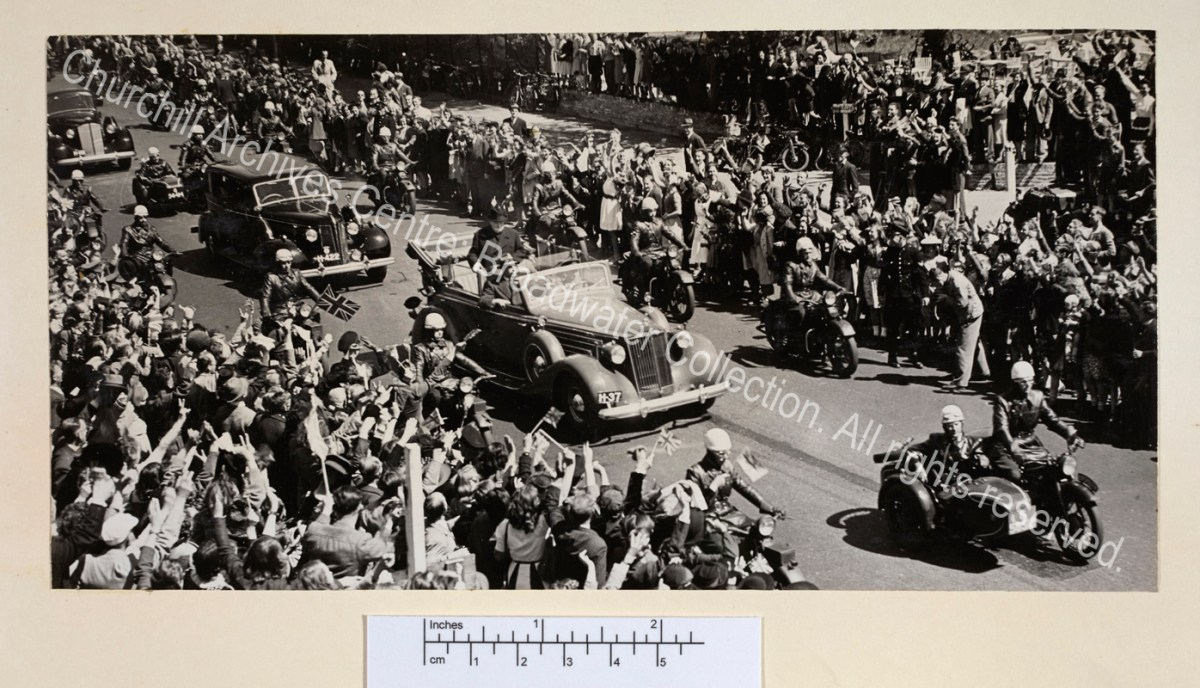 Photo taken from above showing WSC standing in an open topped car escorted by police on motorbikes. The sides of the street are crowded with people waving.