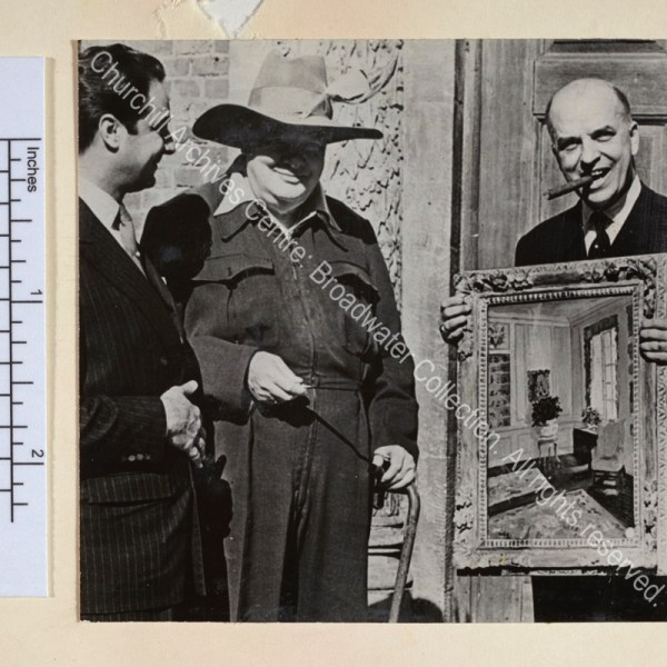 """Photo shows WSC at the Chartwell entrance wearing a siren suit and a broad-brimmed sombrero hat with a feather in it. He is presenting his painting """"The Blue Room"""