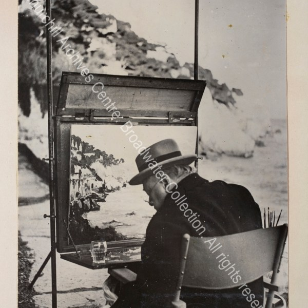 Photo taken from behind shows WSC painting near Cap d'Ail [France] with a glass resting on his painting table.
