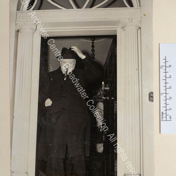 Photo shows WSC at the entrance of a grand property. He is wearing an overcoat and reaching for his hat. CSC is just seen smiling behind him.