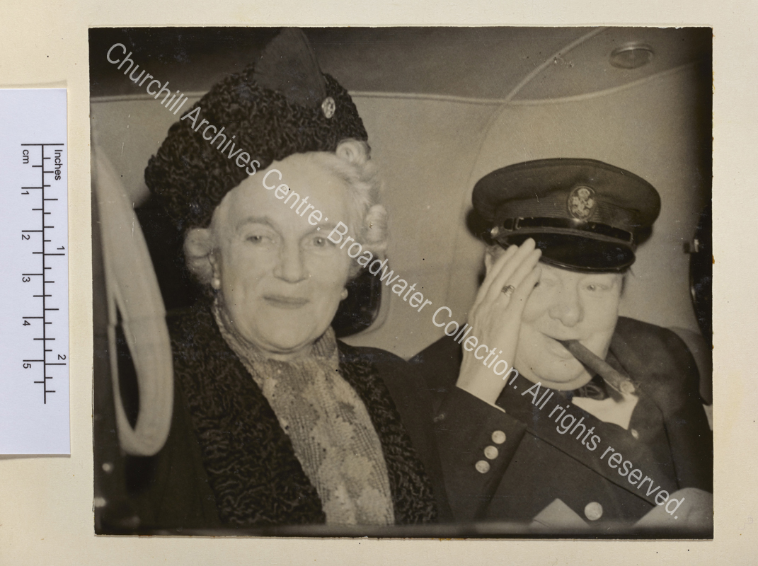 Photo shows WSC sitting together in the back of a car. WSC has a cigar in his mouth and raises his hand to his peaked cap.