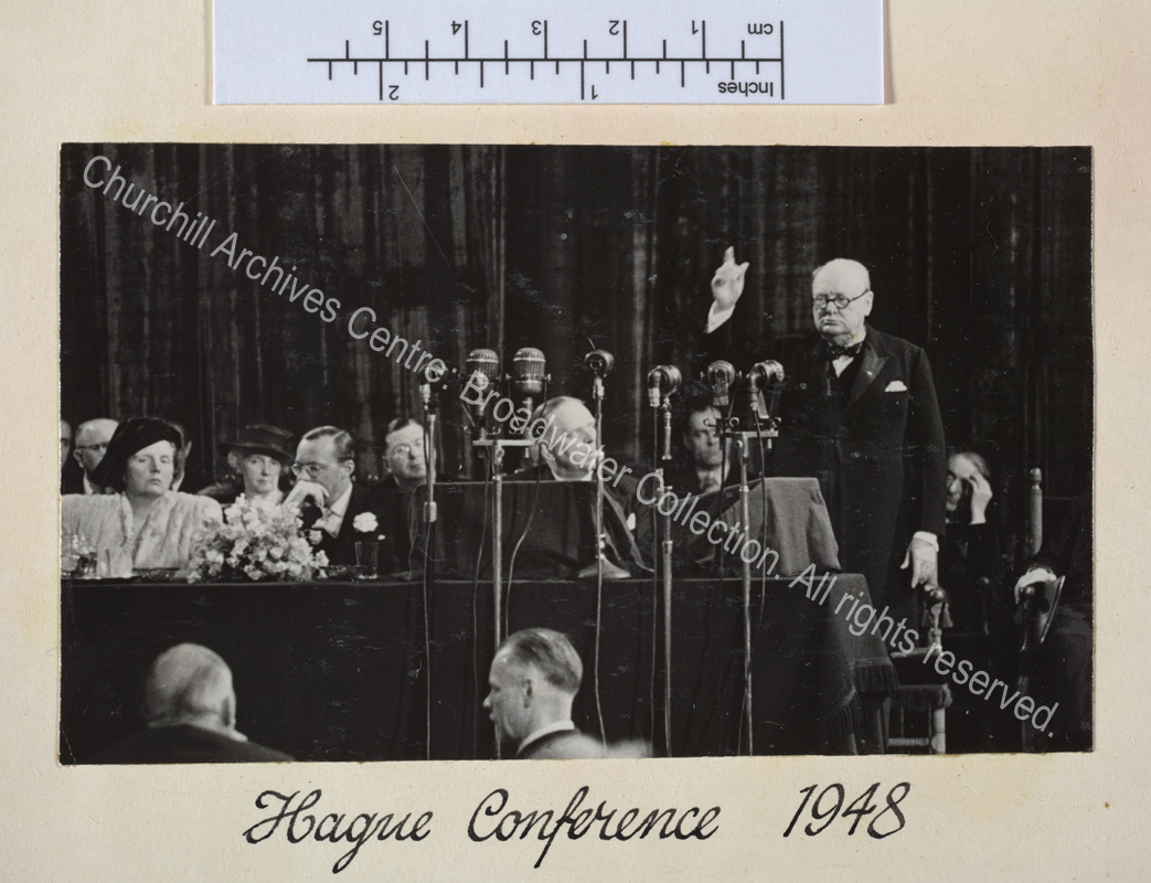Photo of WSC speaking in front of a bank of microphones with his arm raised high.