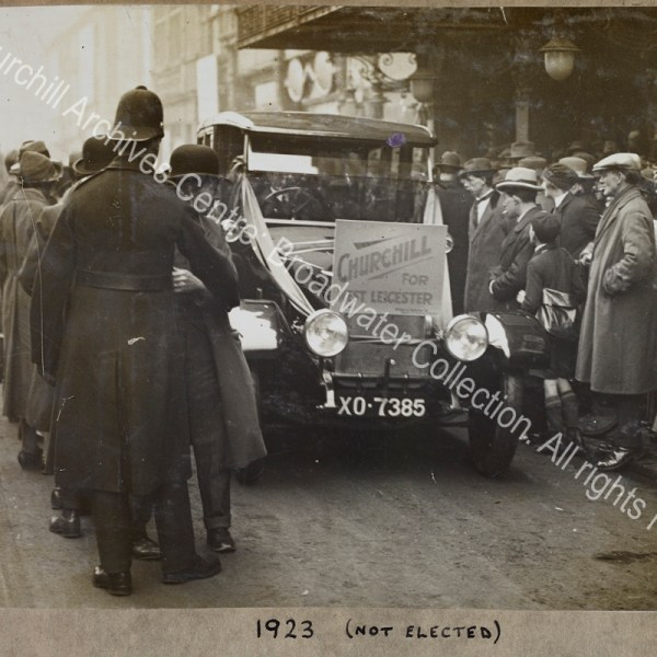 "Photograph of a Wolseley car (registration XO 7385) used during the General Election for WSC's unsuccessful campaign to return to Parliament as MP for West Leicester.  The car has the sign ""Churchill for West Leicester"" on the front and is driving along a street with crowds of people on either side looking in [presumably with WSC inside"