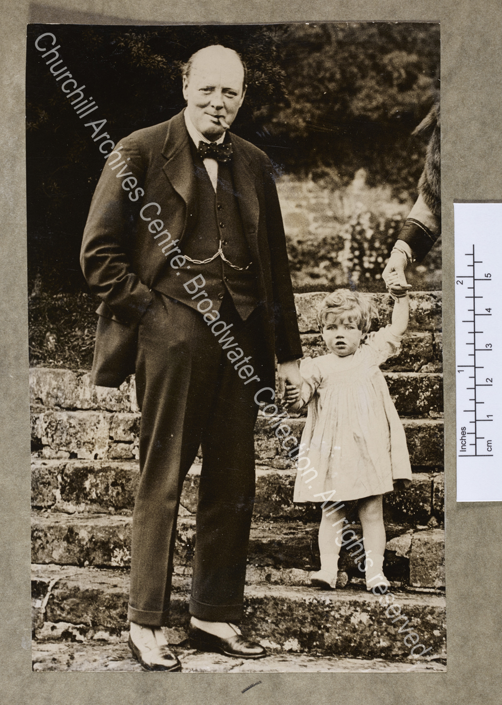 Photograph of WSC standing on the steps of the garden at Chartwell [Kent] holding the hand of Mary Churchill [later Mary Soames] as a toddler.  WSC