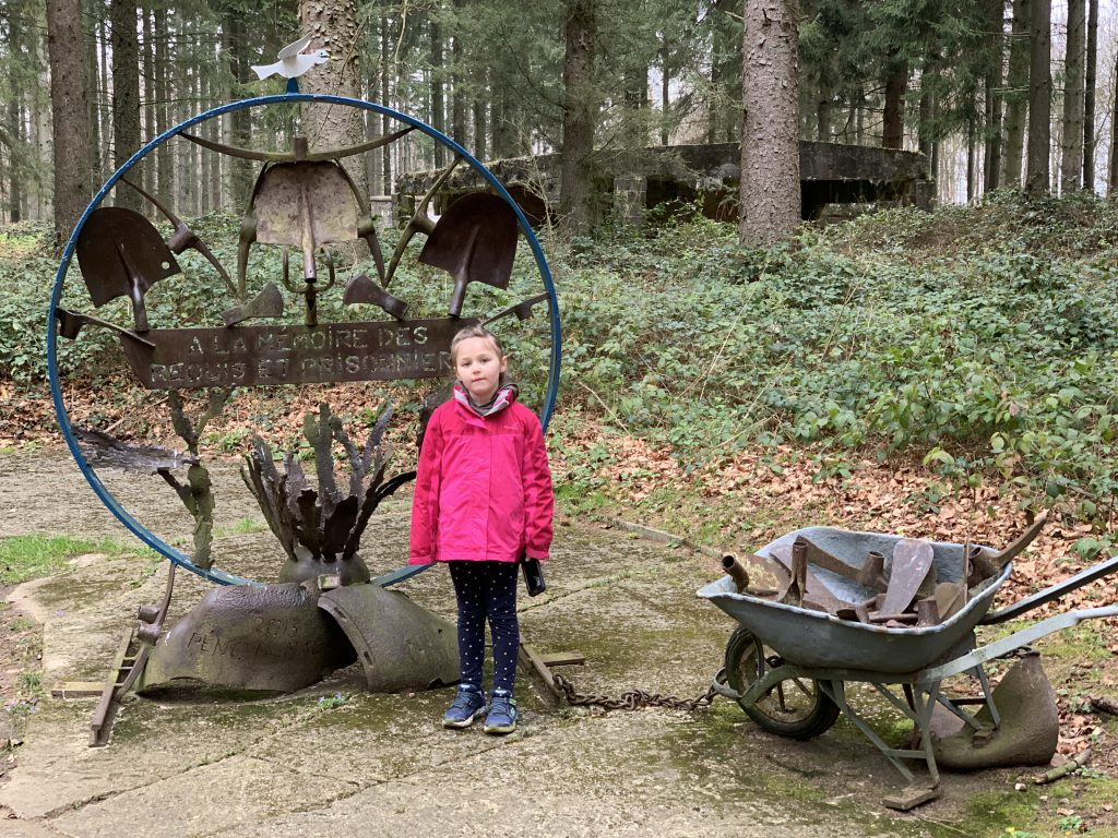 Olivia stands next to a memorial, made from old rusted tools and a wheel barrow. A caption reads 'A la memoire des Requis et Prisonnier'