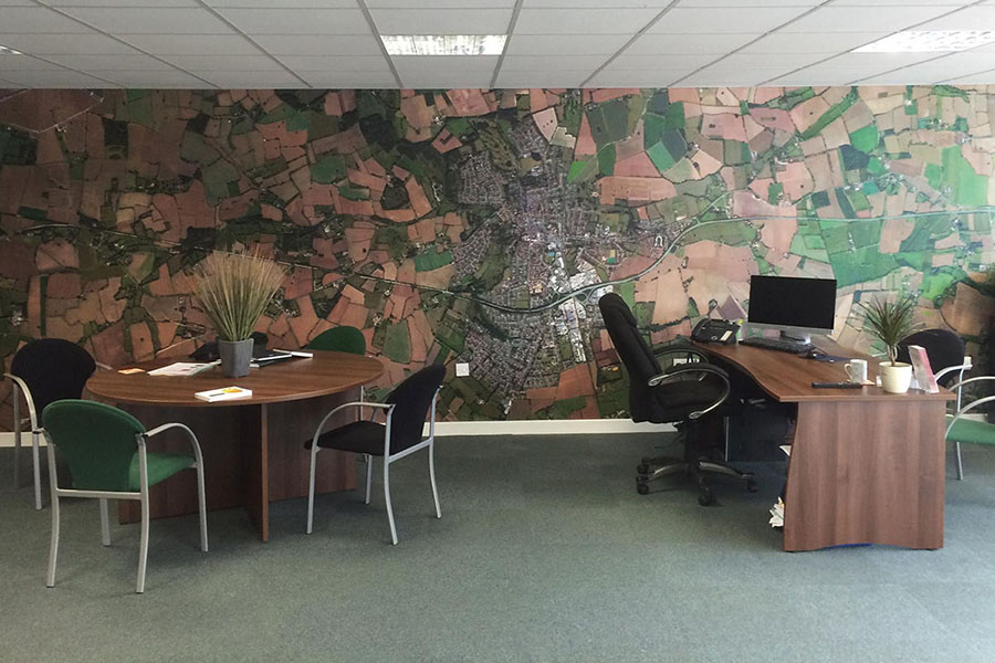 Satellite map wallpaper in an office with desk and chairs
