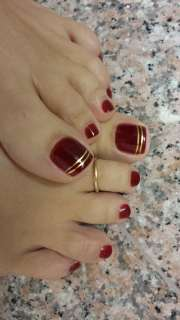 red toenails with simple gold stripes