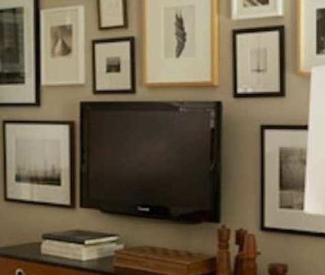 Make Use Of A Large Wall Space By Creating A Gallery Wall That Includes The Television Hidden In Plain Sight Among Prints Paintings And Photos