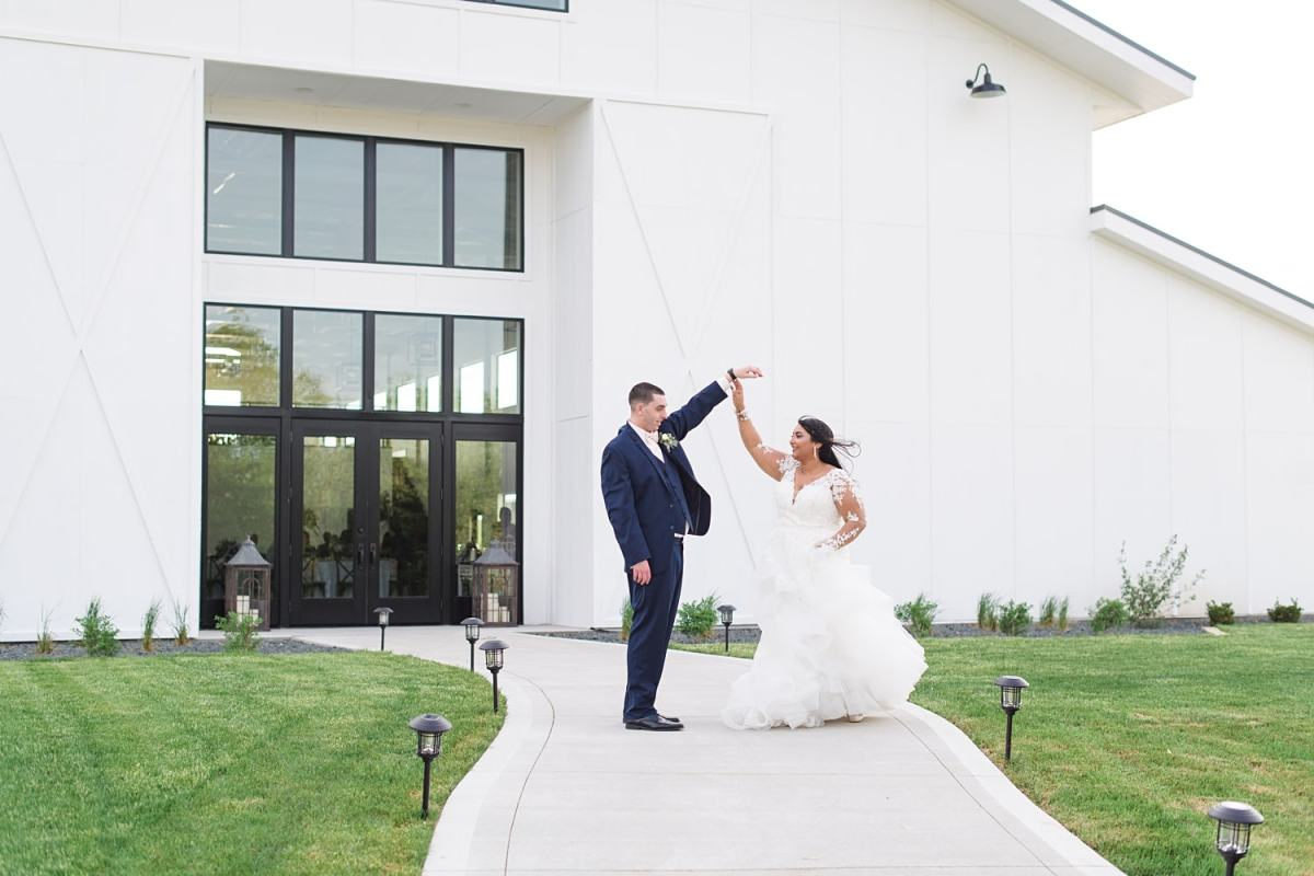 Bride and groom twirl in front of Emerald Hills Events reception venue